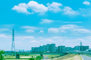 送電鉄塔とマンション群を望む荒川河川敷の写真素材 [FYI02433870]