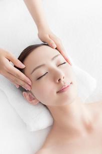 ベッドに仰向けで頭にマッサージを受ける女性の写真素材 [FYI02434063]
