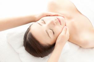 ベッドに仰向けで顔にマッサージを受ける女性の写真素材 [FYI02434208]