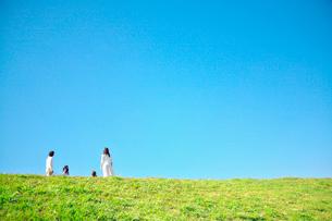 土手の上で空を見上げる家族の写真素材 [FYI02434757]