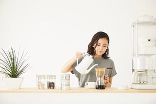 キッチンカウンターでコーヒーを入れる女性の写真素材 [FYI02436085]