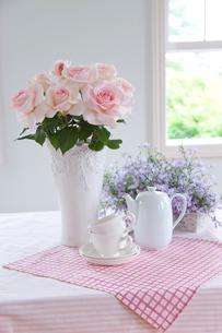 白い花瓶のピンクのバラの花とティーカップの写真素材 [FYI02437712]