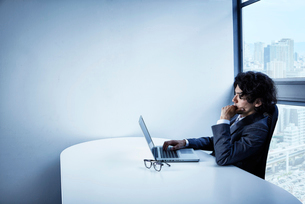 会社のデスクで頭を悩ませるビジネスマンの写真素材 [FYI02437868]
