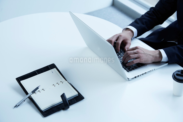 パソコンに向かう男性とテーブルの上のシステム手帳の写真素材 [FYI02437875]