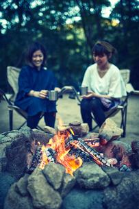 たき火のそばでコーヒーを飲んでいる二人の写真素材 [FYI02437884]
