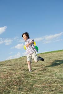 風船を持って走る男の子の写真素材 [FYI02439513]