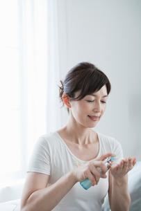 化粧品を手に取る40代女性の写真素材 [FYI02439683]