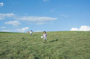 風船を持って走る男の子と女の子の写真素材 [FYI02439872]