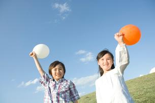 風船を持ち笑顔の男の子と女の子の写真素材 [FYI02440252]