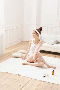 ルームウェア姿でストレッチをする女性の写真素材 [FYI02442471]