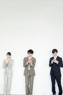 携帯電話を使うスーツ姿の男性と女性の写真素材 [FYI02443050]