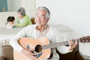 ギターを弾くシニア男性の写真素材 [FYI02443528]