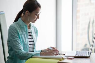 カフェで音楽を聴き勉強をする20代女性の写真素材 [FYI02444269]