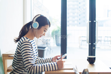 カフェで音楽を聴く20代女性の写真素材 [FYI02444334]