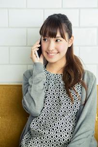 部屋で電話をする20代女性の写真素材 [FYI02444601]