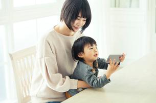 リビングで携帯を覗く親子の写真素材 [FYI02444641]