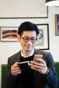 カフェでスマホを見る30代男性の写真素材 [FYI02444756]