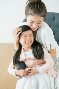 母親に抱きしめられる笑顔の親子の写真素材 [FYI02444849]