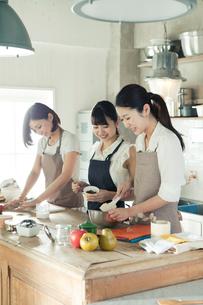 お菓子作りをする20代女性3人の写真素材 [FYI02444956]
