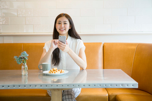 カフェにいる20代女性の写真素材 [FYI02445234]