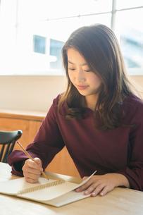 部屋で勉強をする笑顔の20代女性の写真素材 [FYI02445321]