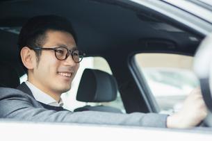 車を運転する笑顔の30代男性の写真素材 [FYI02445390]