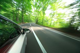 新緑の道を走るハイブリッドカーの写真素材 [FYI02447418]