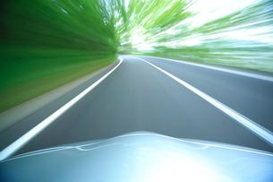 新緑の道を走るハイブリッドカーのボンネットの写真素材 [FYI02447440]