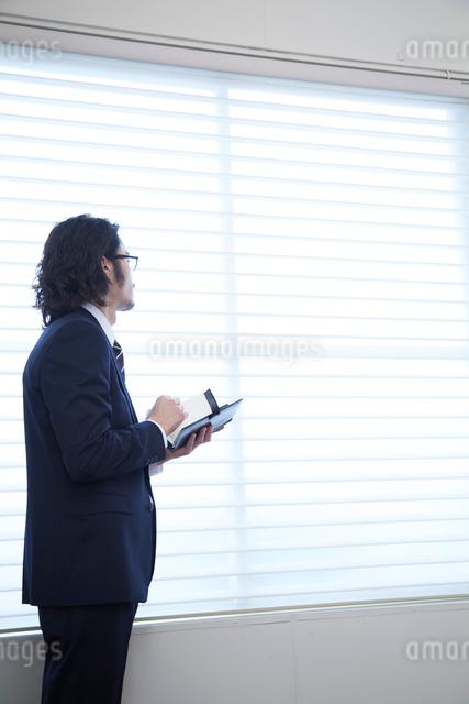 会社の窓際で手帳を開く男性の写真素材 [FYI02447489]