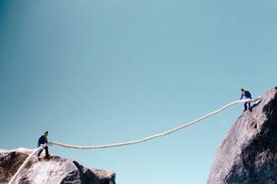 2つの岩山の上でロープを引き合う男性の写真素材 [FYI02447538]