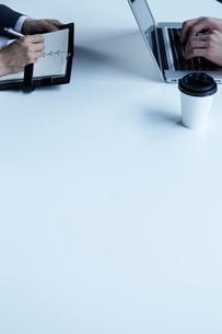 テーブルで仕事をする二人の男性の写真素材 [FYI02447544]