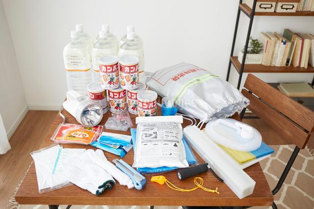 テーブルの上に置かれた水とカンパンと防災グッズの写真素材 [FYI02447550]