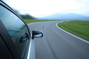 新緑の道を走るハイブリッドカーの写真素材 [FYI02447563]