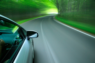 新緑の道を走るハイブリッドカーの写真素材 [FYI02447567]