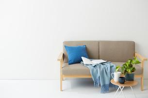 ソファの上にあるブルーのクッションとブランケットの写真素材 [FYI02447579]