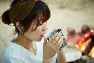 外で暖かいコーヒーを飲む女性の写真素材 [FYI02447591]