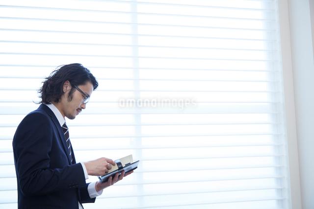 会社の窓際で手帳を見る男性の写真素材 [FYI02447610]