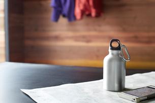 山小屋の中の机に置かれた水筒と地図と携帯電話の写真素材 [FYI02447649]