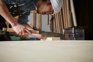 ノコギリで木材を切る人の写真素材 [FYI02447665]