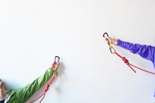 白い壁の前でロープを持ち体を伸ばしてカラビナを引っ掛けようとする2人の登山者の写真素材 [FYI02447870]