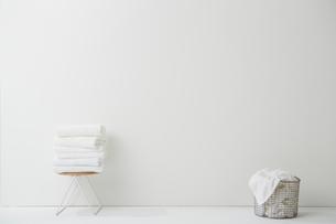 白い空間に置かれた畳まれたタオルと洗濯物の写真素材 [FYI02447878]