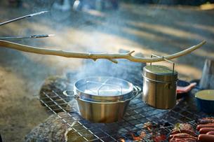 アミの上に置かれたダッチオーブンと飯盒と食材などの写真素材 [FYI02447985]