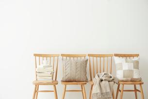 四脚の並べられた椅子とその上に置かれたクッションと本とブランケットの写真素材 [FYI02447988]