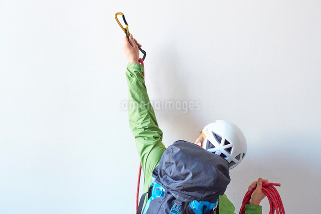 白い壁の前でロープを持ちカラビナを引っ掛けようとするリュックを背負った登山者の写真素材 [FYI02448084]