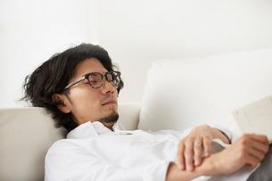 ソファーに横になる男性の写真素材 [FYI02448105]