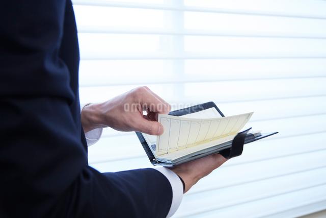 会社の窓際で手帳を開く男性の写真素材 [FYI02448169]