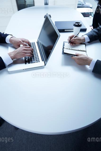 テーブルで仕事をする二人の男性の写真素材 [FYI02448192]
