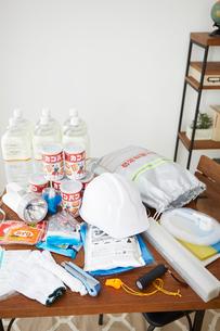 テーブルの上に置かれた水とカンパンと防災グッズの写真素材 [FYI02448332]