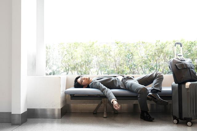ベンチで寝転ぶサラリーマンの写真素材 [FYI02448398]