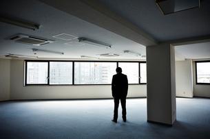 何もないオフィスで下を向き立ちすくむ男性の写真素材 [FYI02448420]
